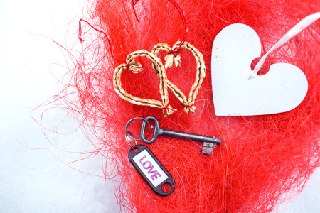 Flat lay hearts made of woven of willow twigs and steel key blank with violet Love text sign . Concept of path to heart. Valentines Day , 14 February. Red texture fibres Background , copy paste space.