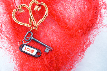 Flat lay hearts made of woven of willow twigs and steel key blank with orange Love text sign . Concept of path to heart. Valentines Day , 14 February. Red texture fibres Background , copy paste space.