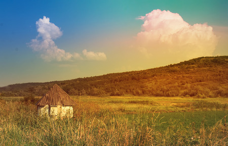 Little white old rural house surrounded by a sunny landscape, summer fresh vital day, hill covered with green grass and huge clouds floating in the sky. Landscape eye-catching view. Concept of travel