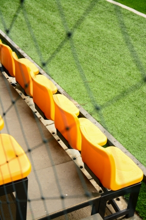 yellow seating on green soccer field  photo