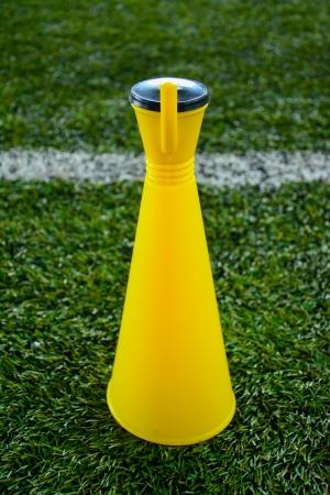 Yellow cheer horn football soccer fan support trumpet on green soccer field photo