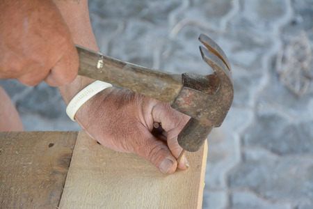 carpenter s hands hitting a nail on the head with old and used wood  photo