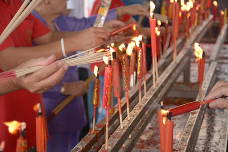 hand cense joss stick  to at an incense burne and burning candle photo