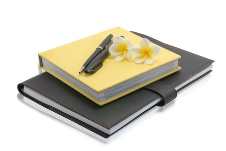 notebook with pen and flower on a white background  photo