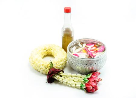 タイはタイのソンクラン祭り用の白い背景で隔離のボウルにジャスミンとバラの花冠と花と水をガーランドします。