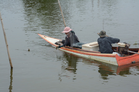 Fishing in wooden boat using  net