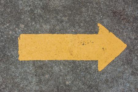 freccia gialla sul pavimento di cemento