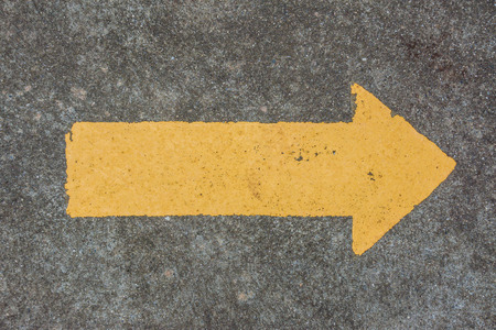 yellow arrow on concrete floor  photo