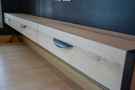 a wooden drawer with balck metal handle