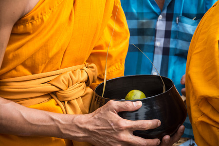 lent: Buddhist monks are given food offering from people for End of Buddhist Lent Day Stock Photo