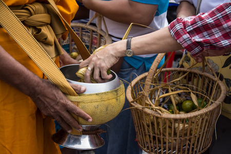 Buddhist monks are given food offering from people for End of Buddhist Lent Day photo