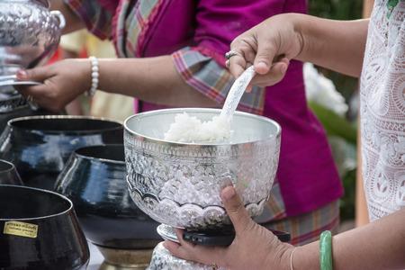limosna: pone ofrendas de comida en un cuenco de las limosnas monje budista Foto de archivo