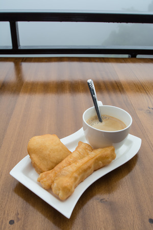 deep-fried doughstick and coffee on wood table,Thai breakfast photo
