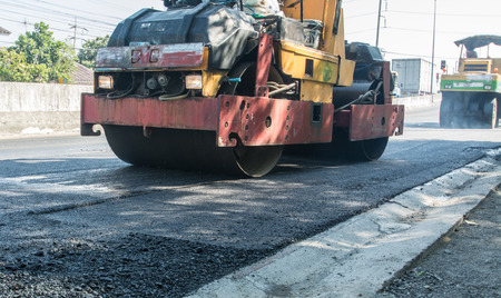 Asphalt roller working on the street that was recently repaired. The highway that has been repaired recently has asphalt. A huge heavy equipment compactor or roller compacting the asphalt road. photo