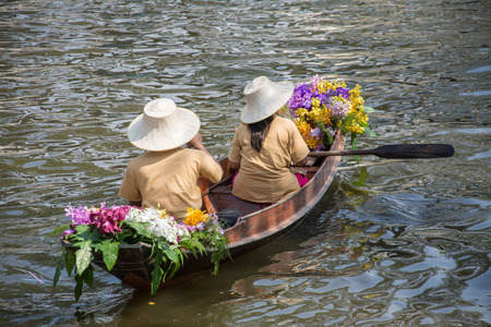 man paddling in the floating market in Thailand photo