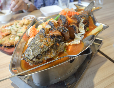 Sour soup made of tamarind paste with fishSour curry with deepfried snake headed fish photo