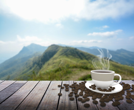 nature backgrounds: Cup with coffee on table over mountains landscape
