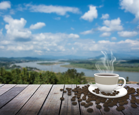 coffee mugs: Cup with tea on table over river