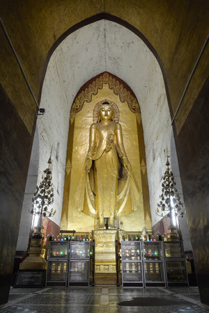 believers: BAGAN, MYANMAR - JULY 30: Standing Buddha Kassapa at the Ananda temple adorned by believers by sticking golden leaves on statue on July 30, 2015 in Bagan, Myanmar.