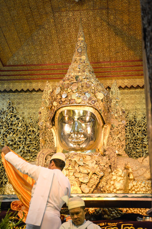 venerate: MANDALAY - AUGUST 01 : Unidentified Burmese monk is cleaning Buddha statue with the golden paper at Mahamuni Buddha temple, August 01, 2015 in Mandalay, Myanmar.