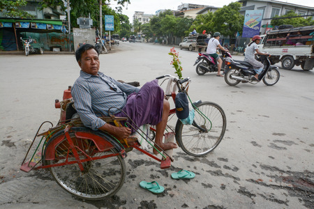 three wheeler: MANDALAY,MYANMAR AUGUST 01; local man sitting in his trishaw in the town of Mandalay, Myanmar on August 01, 2015 Editorial
