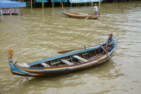 boatman: U Bein Bridge, Myanmar-Aug 02th, 2015: Burmese boatman at U Bein bridge, Taung Tha Man Lake in Amarapura, Mandalay, Myanmar. U Bein bridge is the oldest and longest teakwood bridge in the world. Editorial