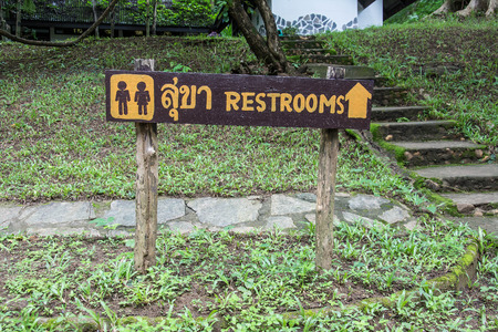 foot path: Wooden sign entrance to the toilet in Thai and English languages.