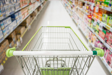 Supermarket interior, empty green shopping cart.