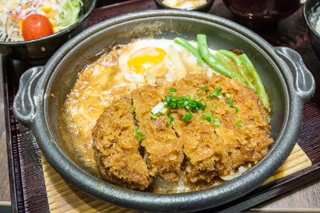 fired egg: Deep Fired pork boiled with fresh egg top on the rice bowl. basic Japanese food Stock Photo