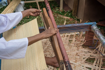 rattan mat: Woman weaving wicker in traditional way at manual loom. Thailand Stock Photo