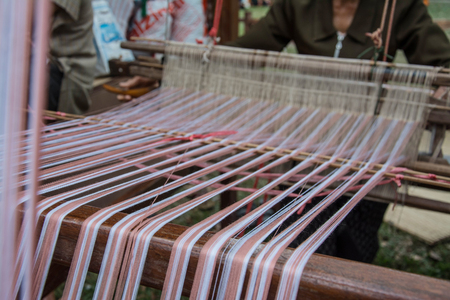 rug weaving: Woman weaving silk in traditional way at manual loom. Thailand