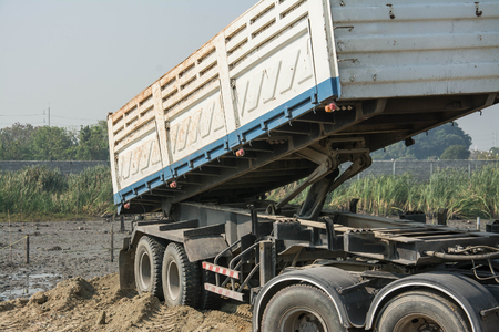dumper truck: Dumper truck unloading soil at construction site