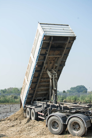 earth moving: Dumper truck unloading soil at construction site