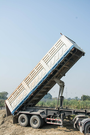 dumper: Dumper truck unloading soil at construction site