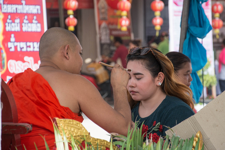 anoint: SUPHANBURI,THAILAND-FEBRUARY 22 ,2016 : Unidentified monk anoints holy powder on Buddhist forehead at wat Palaylai, Suphanburi, on February 22,2016