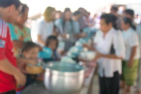 limosna: Resumen imagen borrosa de la oferta alimentaria coloca en un tazón de las limosnas del monje budista