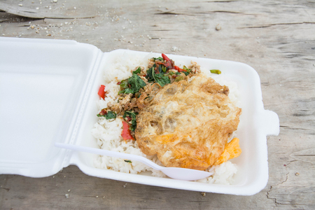 foam box: Basil fried rice with chicken and fried egg in white foam box.