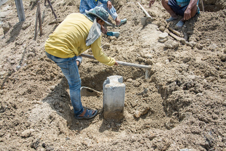 digging: Worker  digging hole with a hoe  at construction site