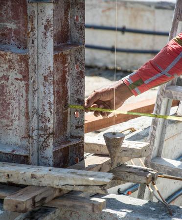 plumb: worker using a plumb bob for check pillar
