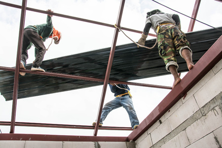 ruberoid: Roofing construction workers  install metal sheet on the roof.