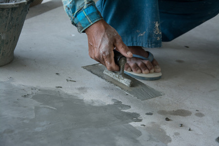 plasterwork: plasterer concrete worker at floor of house construction