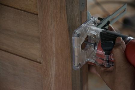 Door installation, worker use electric woodworking router fo rinstalls door knob