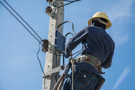青空と電気電柱に取り組んでいる電気技師