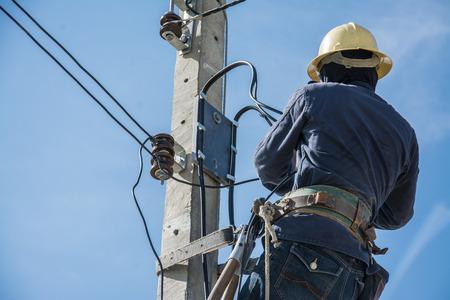 Elektricien werkt aan elektriciteitspool met blauwe lucht