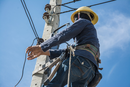 post man: electrician working on electric power pole with blue sky
