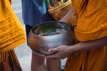 Buddhist monks are given food offering from people for End of Buddhist Lent Day Archivio Fotografico