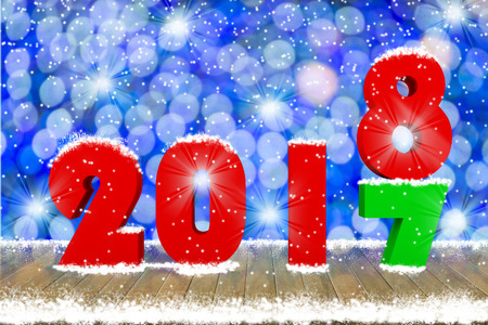 2018 Text on wood table top with snow and decorative light bokeh background