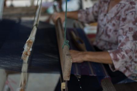 Donna che intreccia la seta in modo tradizionale al telaio manuale. Tailandia Archivio Fotografico - 93000384