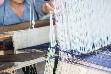 Woman weaving silk in traditional way at manual loom. Thailand
