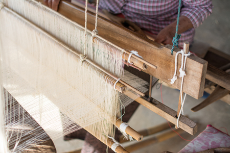 Woman weaving silk in traditional way at manual loom. Thailand